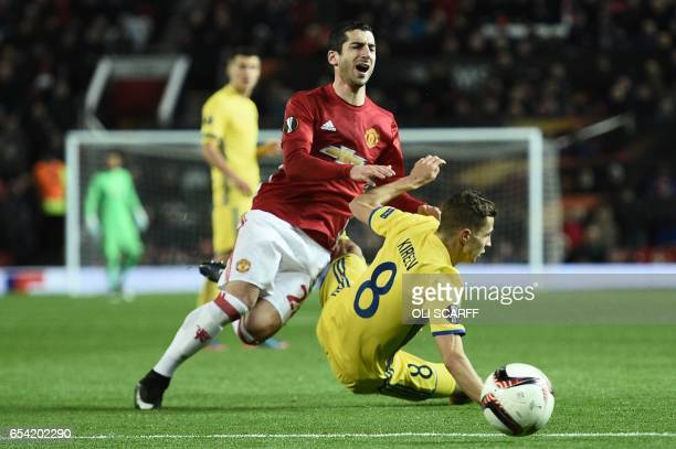 Manchester United's Armenian midfielder Henrikh Mkhitaryan goes down in a challenge with Rostov's Russian midfielder Igor Kireev during the UEFA...