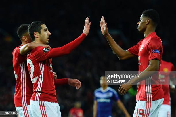 Manchester United's Armenian midfielder Henrikh Mkhitaryan highfives with Manchester United's English striker Marcus Rashford after scoring the...