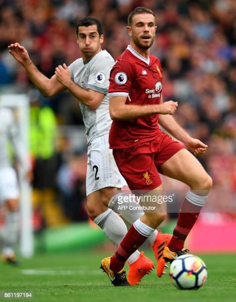Manchester United's Armenian midfielder Henrikh Mkhitaryan vies with Liverpool's English midfielder Jordan Henderson during the English Premier...