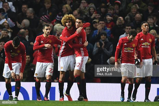 Manchester United's Belgian midfielder Marouane Fellaini celebrates with Manchester United's English defender Chris Smalling after scoring his team's...