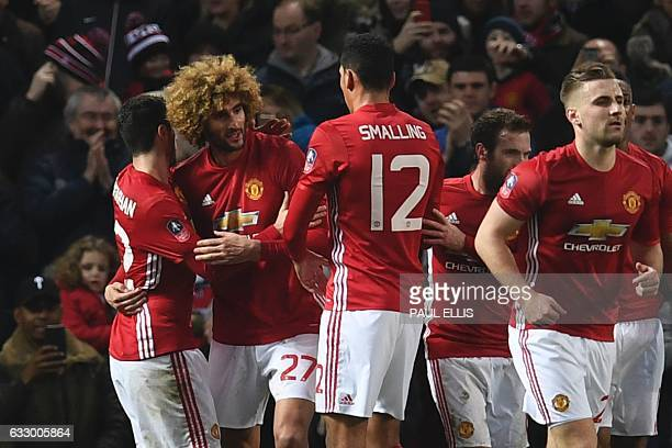 Manchester United's Belgian midfielder Marouane Fellaini celebrates with teammates after scoring his team's first goal during the English FA Cup...