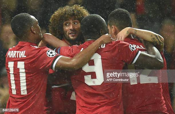 Manchester United's Belgian midfielder Marouane Fellaini celebrates with teammates after scoring the opening goal of the UEFA Champions League Group...