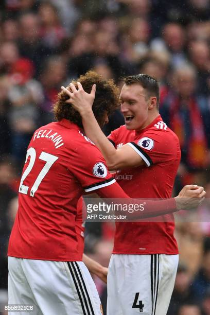Manchester United's Belgian midfielder Marouane Fellaini celebrates with Manchester United's English defender Phil Jones scoring his second and the...