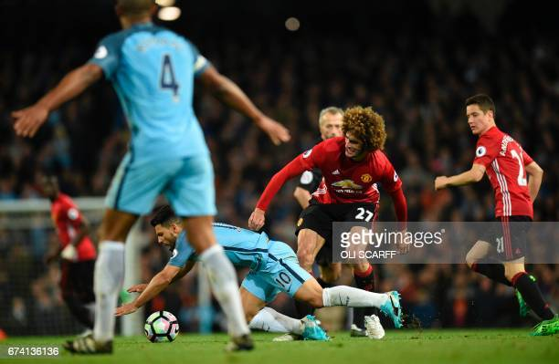 Manchester United's Belgian midfielder Marouane Fellaini fouls Manchester City's Argentinian striker Sergio Aguero to earn a yellow card during the...