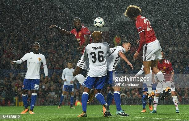 Manchester United's Belgian midfielder Marouane Fellaini heads the opening goal through the rain during the UEFA Champions League Group A football...