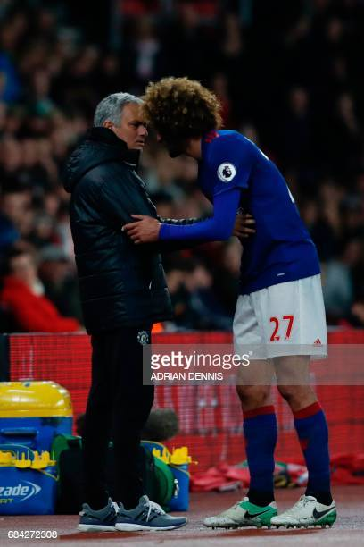 Manchester United's Belgian midfielder Marouane Fellaini talks with Manchester United's Portuguese manager Jose Mourinho during the English Premier...