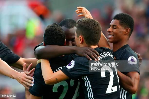 Manchester United's Belgian striker Romelu Lukaku celebrates scoring their second goal with teammates Manchester United's Armenian midfielder Henrikh...