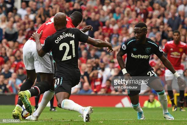 Manchester United's Belgian striker Romelu Lukaku clases with West Ham United's Italian defender Angelo Ogbonna in the penalty area during the...