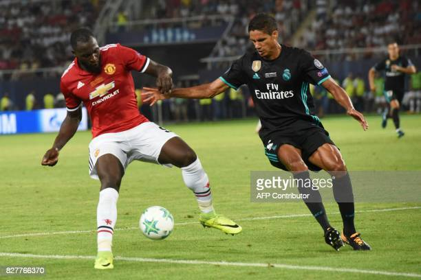 Manchester United's Belgian striker Romelu Lukaku vies with Real Madrid's French defender Raphael Varane during the UEFA Super Cup football match...