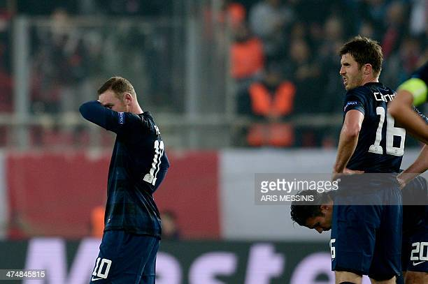 Manchester United's British forward Wayne Rooney and British midfielder Michael Carrick react after Olympiakos scored a second goal during the round...