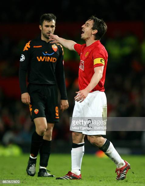 Manchester United's captain Gary Neville celebrates at the end of the game past Roma's Mirko Vucinic who walks away dejected