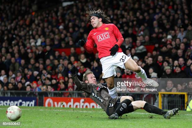 Manchester United's Carlos Tevez and AaB Aalborg's Jeppe Curth battle for the ball