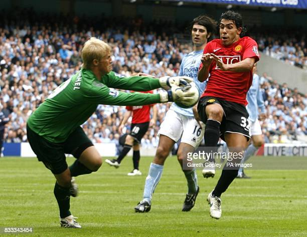 Manchester United's Carlos Tevez and Manchester City goalkeeper Kasper Schmeichel battle for the ball