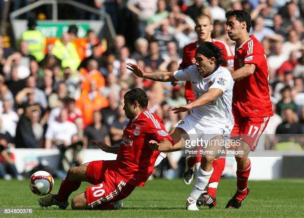 Manchester United's Carlos Tevez battles for the ball with Liverpool's Alvaro Arbeloa and Javier Mascherano