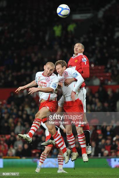 Manchester United's Chris Smalling battles for the ball in the air with Crawley Town's Simon Rusk and Kyle McFadzean