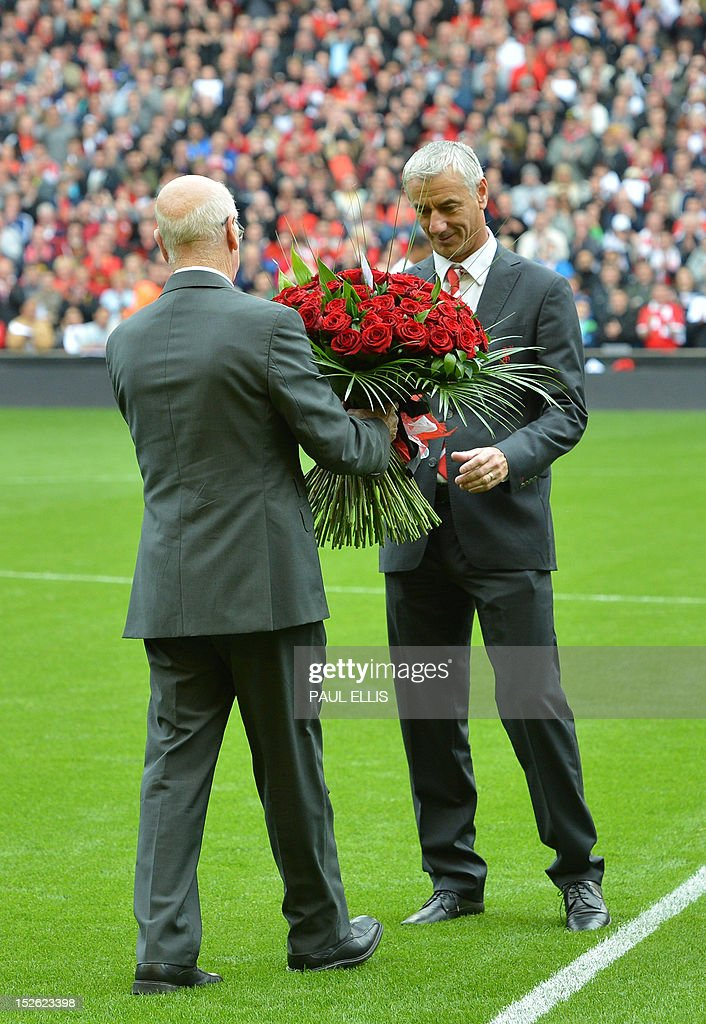 """Manchester United's club ambassador Bobby Charlton (L) hands a bouquet of 96 roses to Liverpool's club ambassador Ian Rush (R) before the English Premier League football match between Liverpool and Manchester United at Anfield in Liverpool, north-west England on September 23, 2012. The 96 roses represent the 96 supporters who died in the 1989 Hillsborough disaster.AFP PHOTO/PAUL ELLIS USE. No use with unauthorized audio, video, data, fixture lists, club/league logos or """"live"""" services. Online in-match use limited to 45 images, no video emulation. No use in betting, games or single club/league/player publications."""