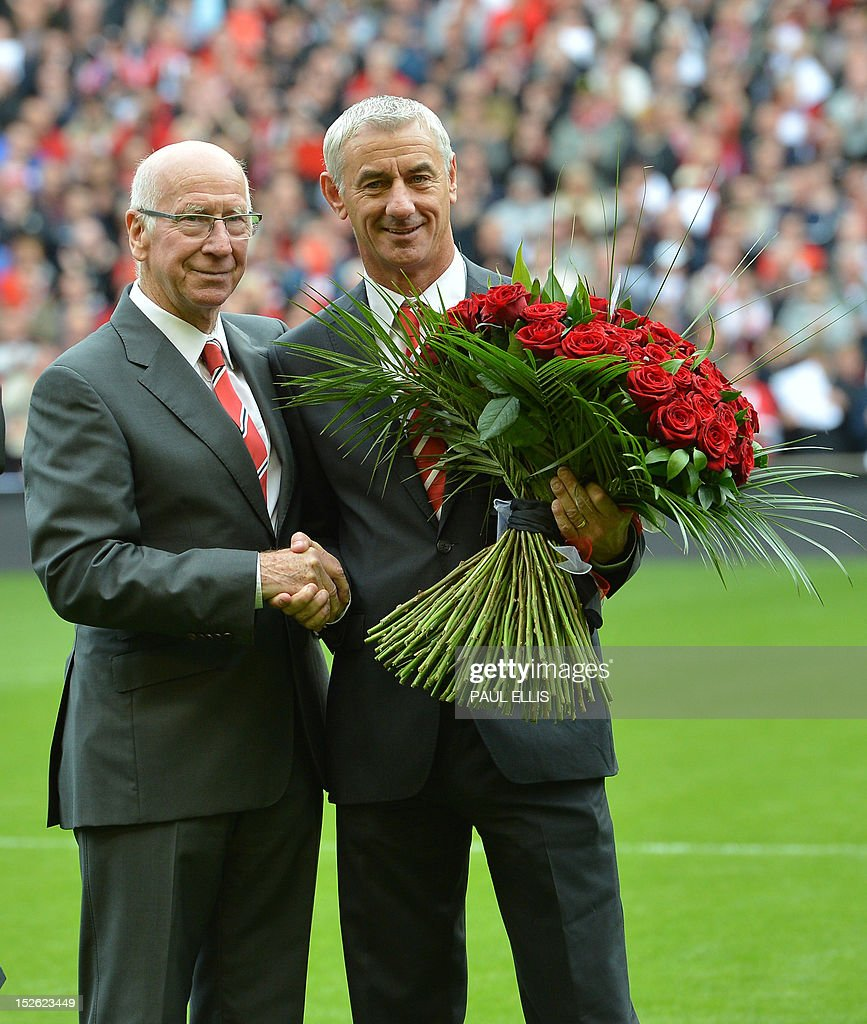"""Manchester United's club ambassador Bobby Charlton (L) hands a bouquet of 96 roses to Liverpool's club ambassador Ian Rush (R) before the English Premier League football match between Liverpool and Manchester United at Anfield in Liverpool, north-west England on September 23, 2012. The 96 roses represent the 96 supporters who died in the 1989 Hillsborough disaster. USE. No use with unauthorized audio, video, data, fixture lists, club/league logos or """"live"""" services. Online in-match use limited to 45 images, no video emulation. No use in betting, games or single club/league/player publications."""