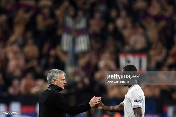 Manchester United's coach from Portugal Jose Mourinho thanks Manchester United's defender from Ivory Coast Eric Bailly after the UEFA Champions...