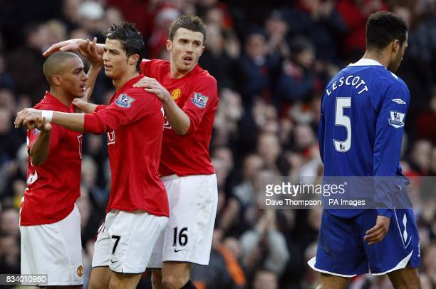 Manchester United's Cristiano Ronaldo celebrates with his team mates after scoring the opening goal of the game as Everton's Joleon Lescott walks...