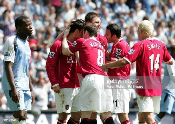 Manchester United's Cristiano Ronaldo is congratulated by his team mates after scoring from the penalty spot as a dejected Nedum Onuoha of Manchester...