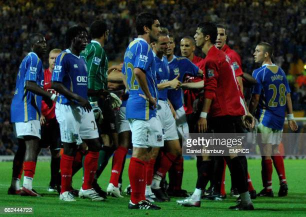 Manchester United's Cristiano Ronaldo walks past Portsmouth's Richard Hughes who he allegedly headbutted