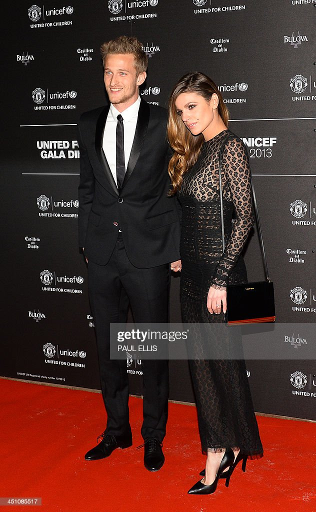 Manchester United's Danish goalkeeper Anders Lindegaard (L) and Misse Beqiri pose for photographs as the arrive for a gala dinner in aid of UNICEF at Old Trafford in Manchester on November 21, 2013.