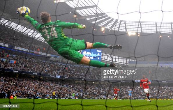 Manchester United's Danish goalkeeper Anders Lindegaard saves a shot from Manchester City's Argentinian forward Sergio Aguero during the FA Cup third...