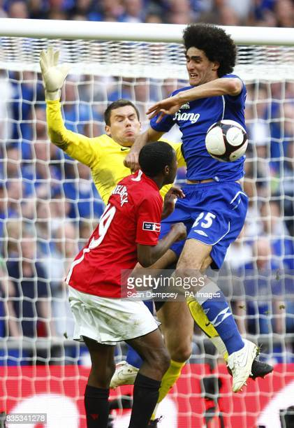 Manchester United's Danny Welbeck and goalkeeper Ben Foester challenge Everton's Marouane Fellaini as he goes for a goal
