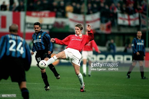 Manchester United's David Beckham and Inter's Roberto Baggio challenge for tha ball