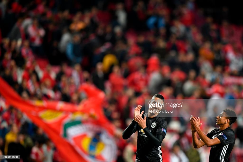 Manchester United's defender Chris Smalling (L) and Manchester United's midfielder Jesse Lingard (R) applaud at the end of the UEFA Champions League group A football match SL Benfica vs Manchester United FC at the Luz stadium in Lisbon on Ocotber 18, 2017. /