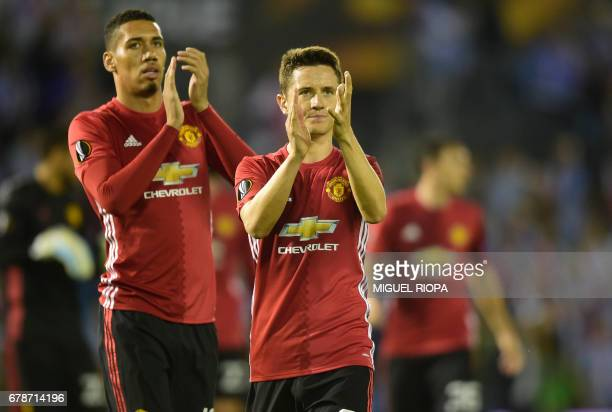 Manchester United's defender Chris Smalling and Spanish midfielder Ander Herrera applaud their fans at the end of their UEFA Europa League semi final...