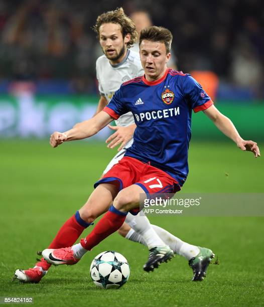 Manchester United's defender from Netherlands Daley Blind and CSKA Moscow's midfielder from Russia Aleksandr Golovin vie for the ball during the UEFA...