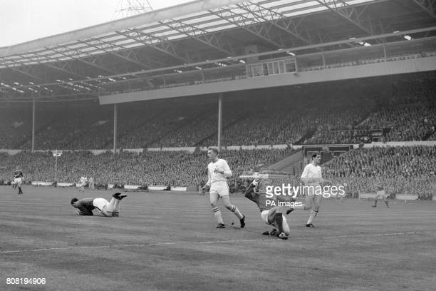 Manchester United's Denis Law second right slides on one knee as Leicester City goalkeeper Gordon Banks pounces on the ball Leicester City defenders...