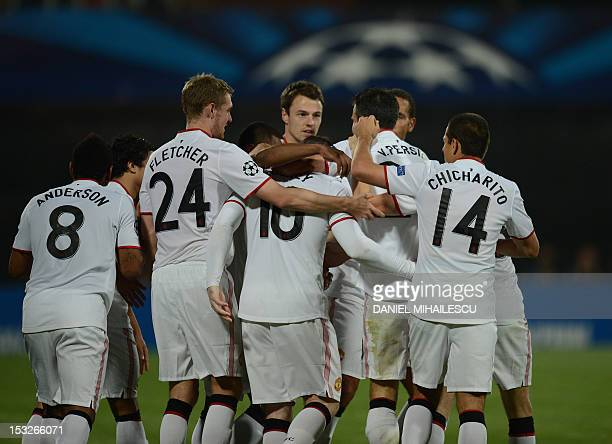 Manchester United's Dutch forward Robin van Persie celebrates after he scored 21 with his teammates during the Champions League Group H football...