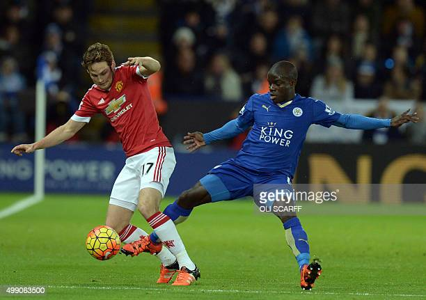 Manchester United's Dutch midfielder Daley Blind vies with Leicester City's French midfielder N'Golo Kante during the English Premier League football...