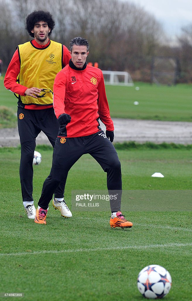 Manchester United's Dutch striker Robin van Persie (R) and Manchester United's Belgian midfielder Marouane Fellaini (L) take part in a training session at their Carrington complex in Manchester, north west England, on February 24, 2014 ahead of the UEFA Champions League football match between Olympiakos and Manchester United on February 25.