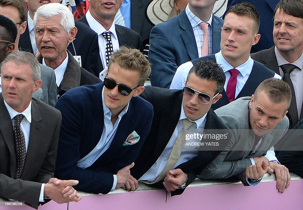 Manchester United's Dutch striker Robin van Persie (C), English defender Phil Jones (R back) and English midfielder Tom Cleverley (R) watch the action at the Chester Races horse racing event at Chester Racecourse in Cheshire, northwest England on May 8, 2013. Alex Ferguson will retire as Manchester United boss at the end of the season, the Premier League champions announced on May 8, ending the most successful managerial reign in English football. AFP PHOTO / ANDREW YATES
