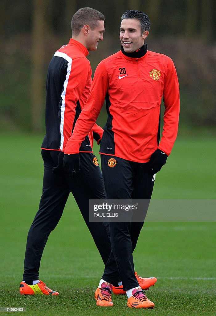 Manchester United's Dutch striker Robin van Persie (R) laughs with Manchester United's Serbian defender Nemanja Vidic (L) during a training session at their Carrington complex in Manchester, north west England, on February 24, 2014 ahead of the UEFA Champions League football match between Olympiakos and Manchester United on February 25.
