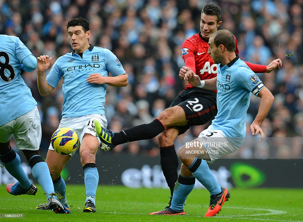 """Manchester United's Dutch striker Robin Van Persie (2nd R) shoots between Manchester City's Argentinian defender Pablo Zabaleta (R) and English midfielder Gareth Barry (L) during the English Premier League football match between Manchester City and Manchester United at The Etihad stadium in Manchester, north-west England on December 9, 2012. USE. No use with unauthorized audio, video, data, fixture lists, club/league logos or """"live"""" services. Online in-match use limited to 45 images, no video emulation. No use in betting, games or single club/league/player publications."""