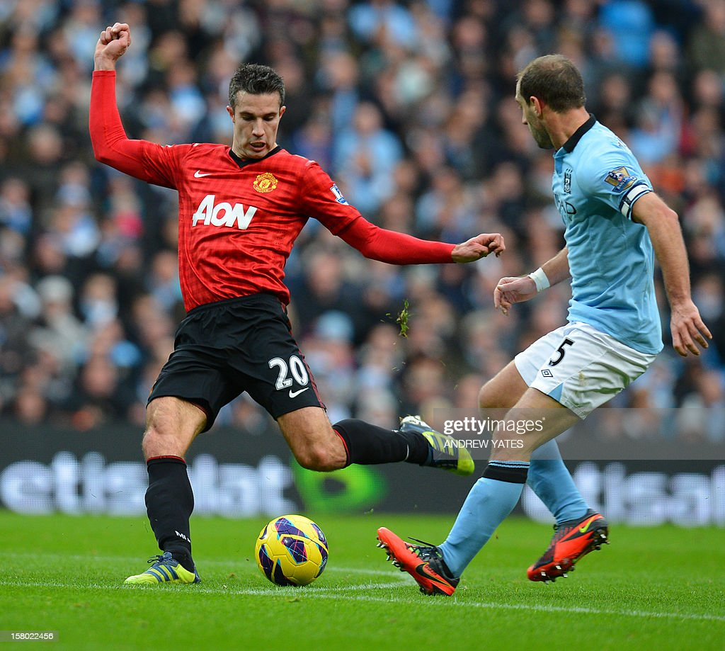 """Manchester United's Dutch striker Robin Van Persie (L) shoots during the English Premier League football match between Manchester City and Manchester United at The Etihad stadium in Manchester, north-west England on December 9, 2012. USE. No use with unauthorized audio, video, data, fixture lists, club/league logos or """"live"""" services. Online in-match use limited to 45 images, no video emulation. No use in betting, games or single club/league/player publications."""