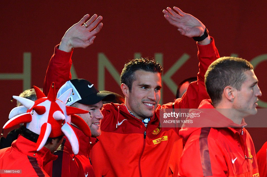 Manchester United's Dutch striker Robin van Persie (C) waves to the crowds as he celebrates with teammates on stage after winning the Premier League title for the 13th time, during the team's victory parade outside the town hall in Manchester, north west England, on May 13, 2013.