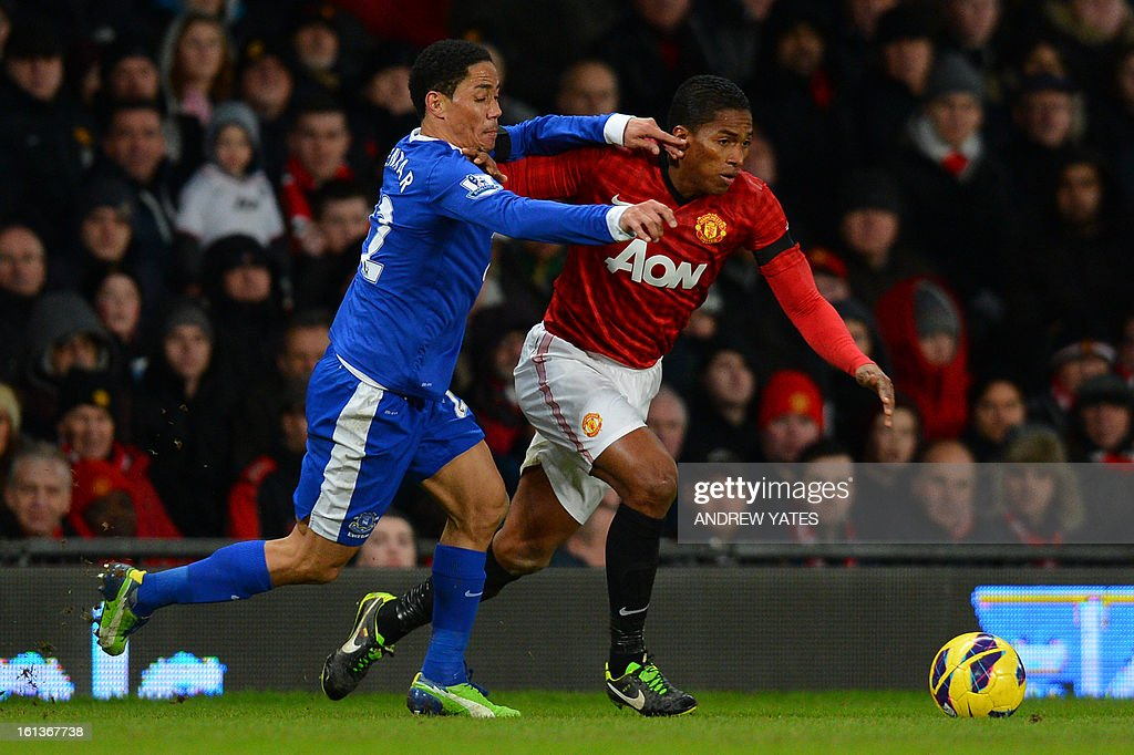 """Manchester United's Ecuador midfielder Antonio Valencia (R) vies with Everton's South African midfielder Steven Pienaar (L) during the English Premier League football match between Manchester United and Everton at Old Trafford, Manchester, North West England, on February 10, 2013. USE. No use with unauthorized audio, video, data, fixture lists, club/league logos or """"live"""" services. Online in-match use limited to 45 images, no video emulation. No use in betting, games or single club/league/player publications."""