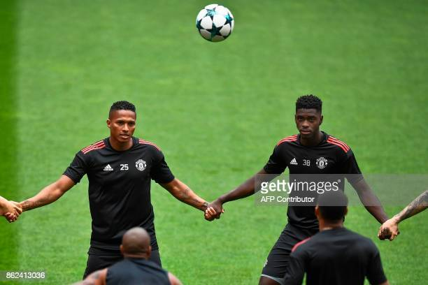 Manchester United's Ecuadorian defender Antonio Valencia and Manchester United's defender Axel Tuanzebe take part in a training session at the Luz...