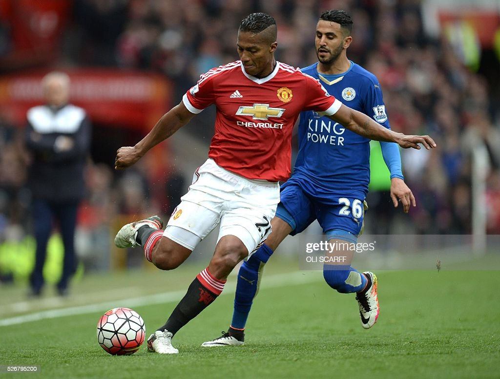 Manchester United's Ecuadorian midfielder Antonio Valencia (L) plays the ball in front of Leicester City's Algerian midfielder Riyad Mahrez (R) during the English Premier League football match between Manchester United and Leicester City at Old Trafford in Manchester, north west England, on May 1, 2016. / AFP / OLI SCARFF / RESTRICTED TO EDITORIAL USE. No use with unauthorized audio, video, data, fixture lists, club/league logos or 'live' services. Online in-match use limited to 75 images, no video emulation. No use in betting, games or single club/league/player publications. /