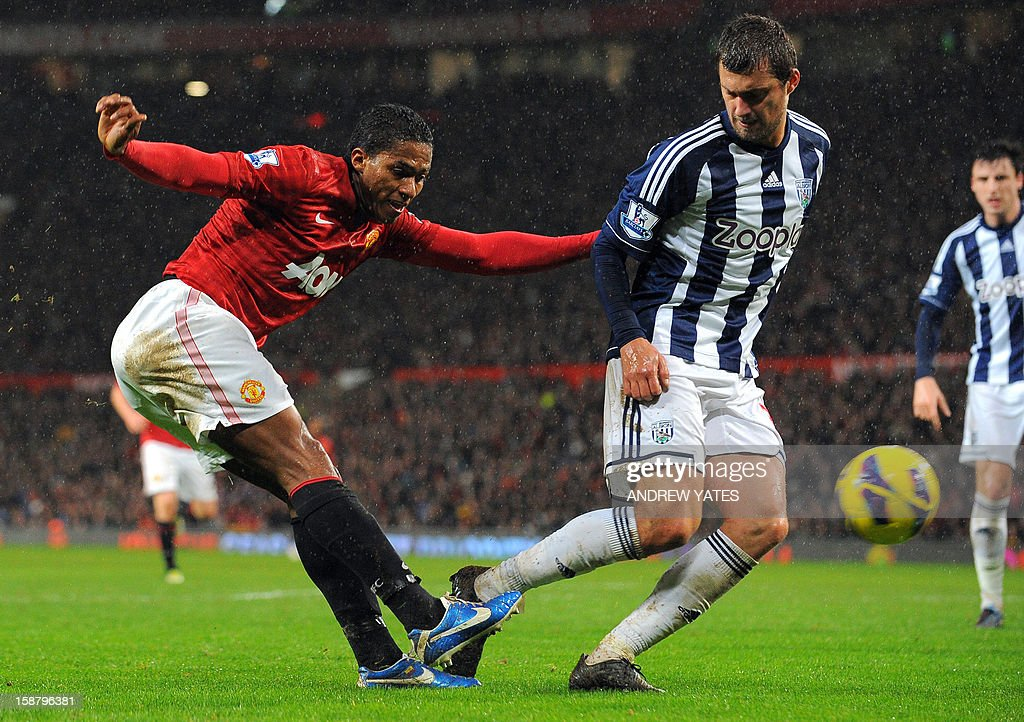 "Manchester United's Ecuadorian midfielder Antonio Valencia (L) shoots past West Bromwich Albion's Romanian defender Gabriel Tamas during the English Premier League football match between Manchester United and West Bromwich Albion at Old Trafford in Manchester, north-west England on December 29, 2012. Manchester United won the match 2-0. AFP PHOTO/ANDREW YATES USE. No use with unauthorized audio, video, data, fixture lists, club/league logos or ""live"" services. Online in-match use limited to 45 images, no video emulation. No use in betting, games or single club/league/player publications"