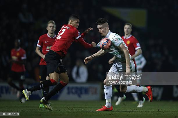 Manchester United's English defender Chris Smalling grabs the shirt of Yeovil Town's English striker Kieffer Moore during the English FA Cup third...