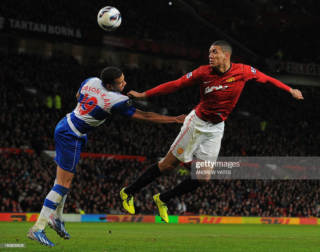"""Manchester United's English defender Chris Smalling (R) heads past Reading's Welsh forward Hal Robson-Kanu during the English Premier League football match between Manchester United and Reading at Old Trafford in Manchester, north-west England on March 16, 2013. Manchester United won 1-0.AFP PHOTO/ANDREW YATES RESTRICTED TO EDITORIAL USE. No use with unauthorized audio, video, data, fixture lists, club/league logos or """"live"""" services. Online in-match use limited to 45 images, no video emulation. No use in betting, games or single club/league/player publications."""