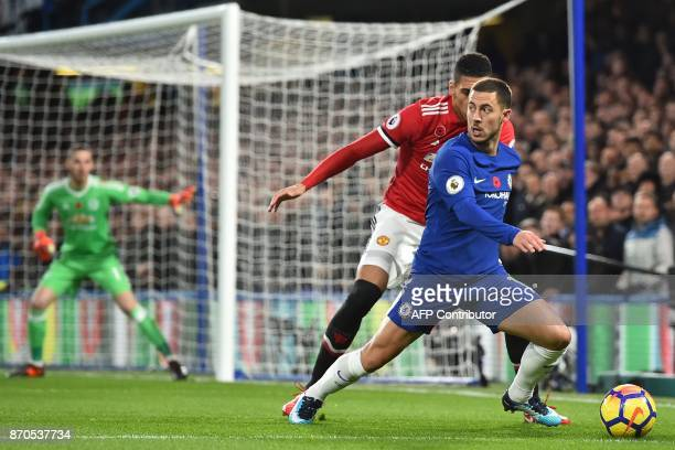 Manchester United's English defender Chris Smalling vies with Chelsea's Belgian midfielder Eden Hazard during the English Premier League football...