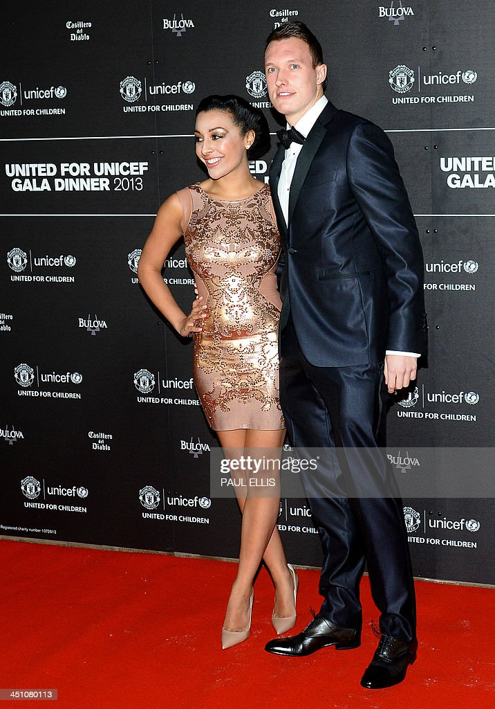 Manchester United's English defender Phil Jones (R) and his partner Kaya Hall pose for photographs as they arrive for a gala dinner in aid of UNICEF at Old Trafford in Manchester on November 21, 2013.
