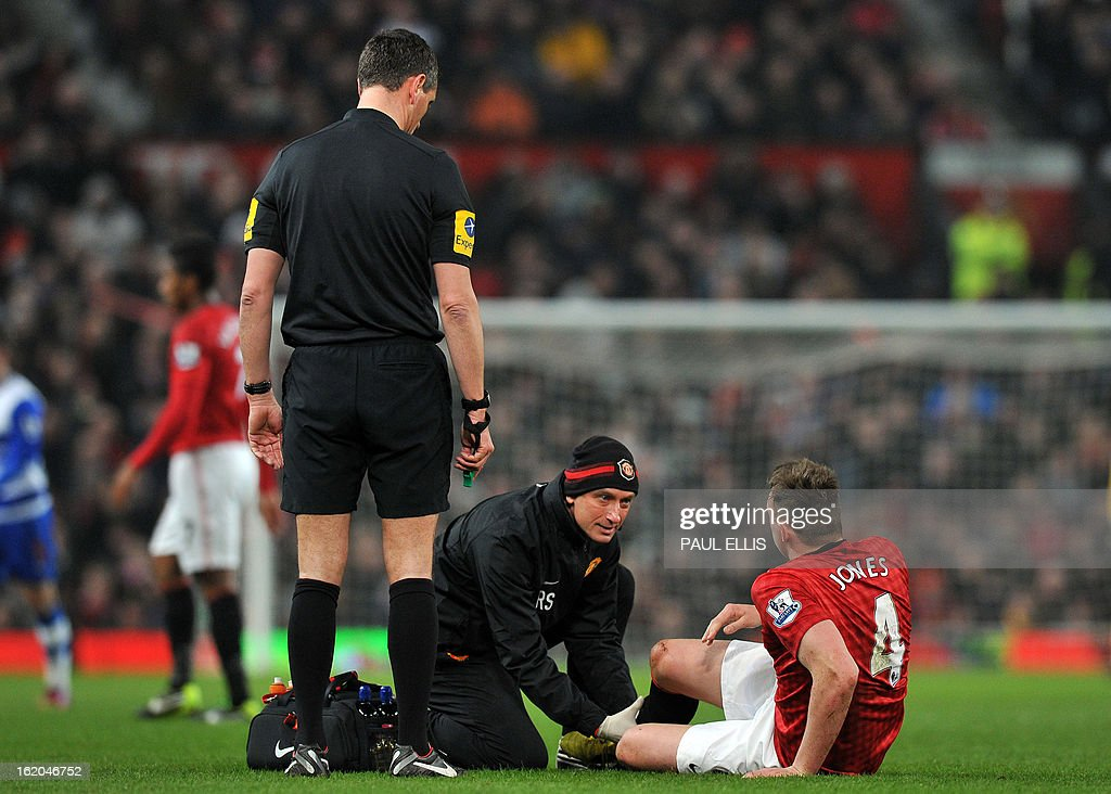 """Manchester United's English defender Phil Jones receives treatment on the field before being substituted during the English FA Cup fifth round football match between Manchester United and Reading at Old Trafford in Manchester, north west England, on February 18, 2013. USE. No use with unauthorized audio, video, data, fixture lists, club/league logos or """"live"""" services. Online in-match use limited to 45 images, no video emulation. No use in betting, games or single club/league/player publications."""